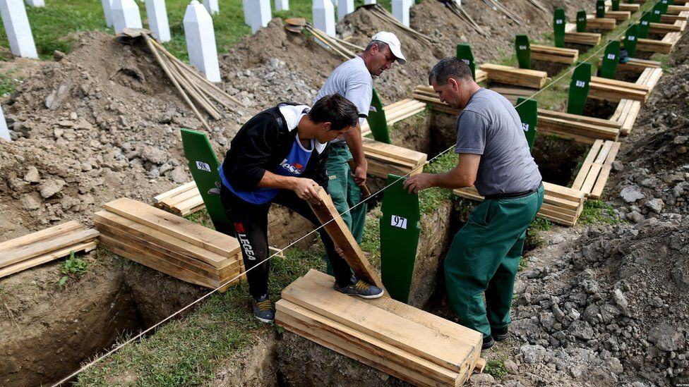 Workers prepare graves for burial in Potocari Cemetery on 10 July 2015