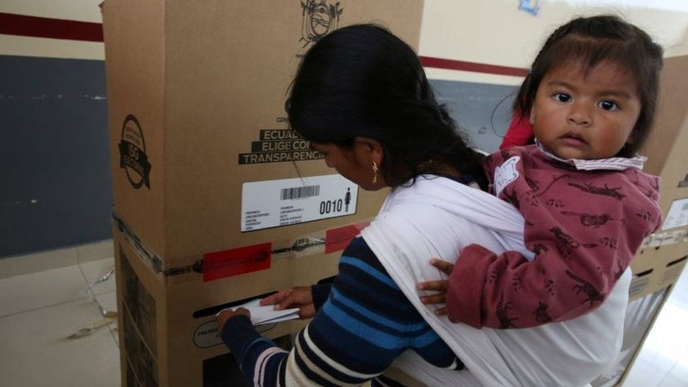 A girl looks on as her mother casts her vote during the presidential election at a school-turned-polling station in Quito, Ecuador February 19, 2017
