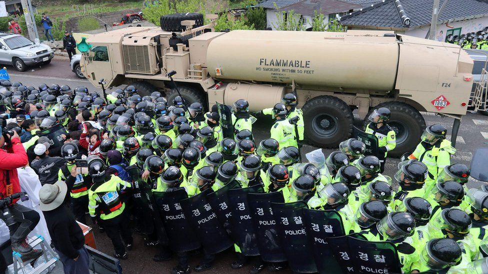 riot police surrounding a Thaad missile system as it is transported