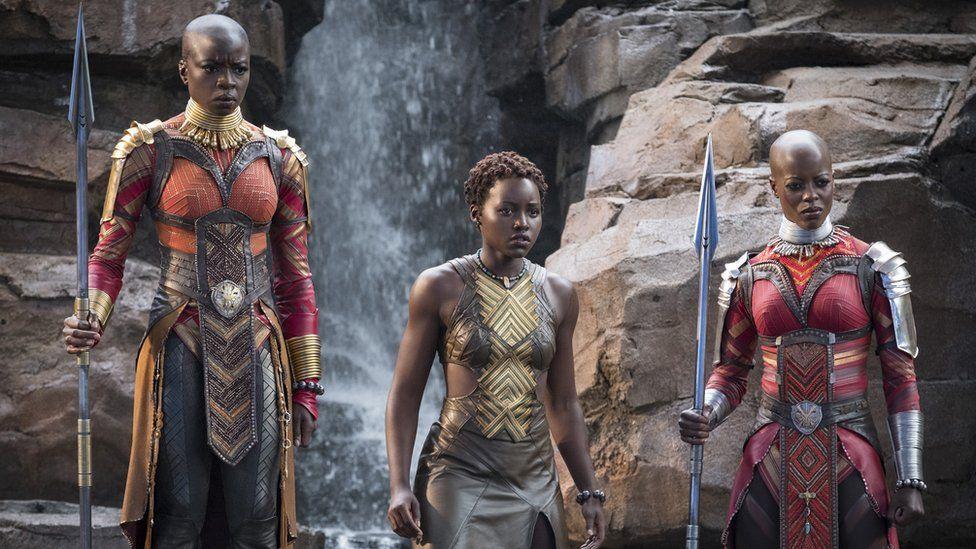 Movie still of three women warriors of Wakanda in armour holding spears.