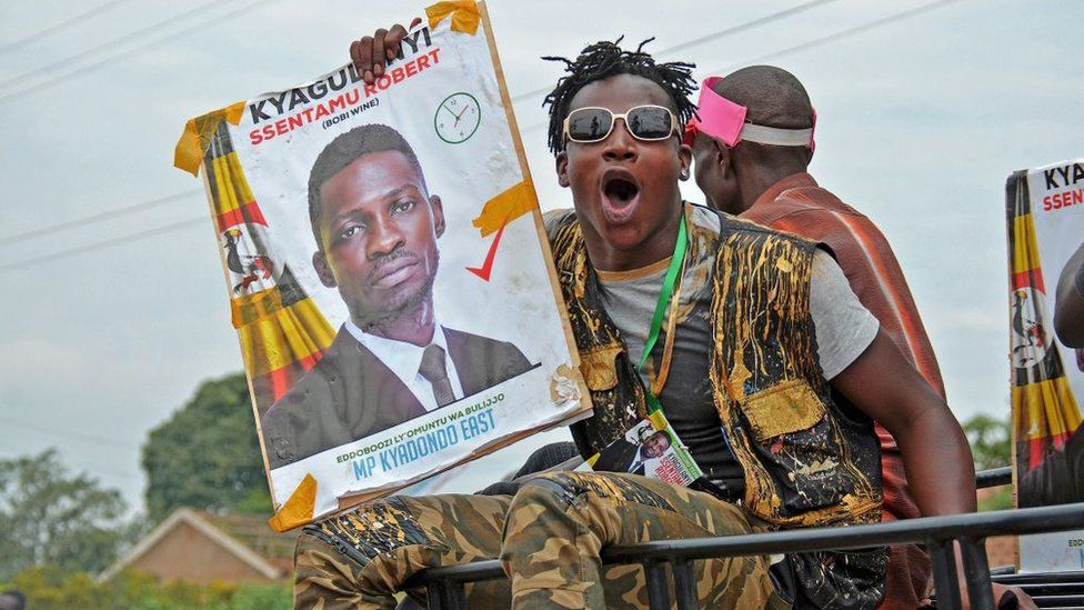 Bobi Wine's supporter holds his campaign poster