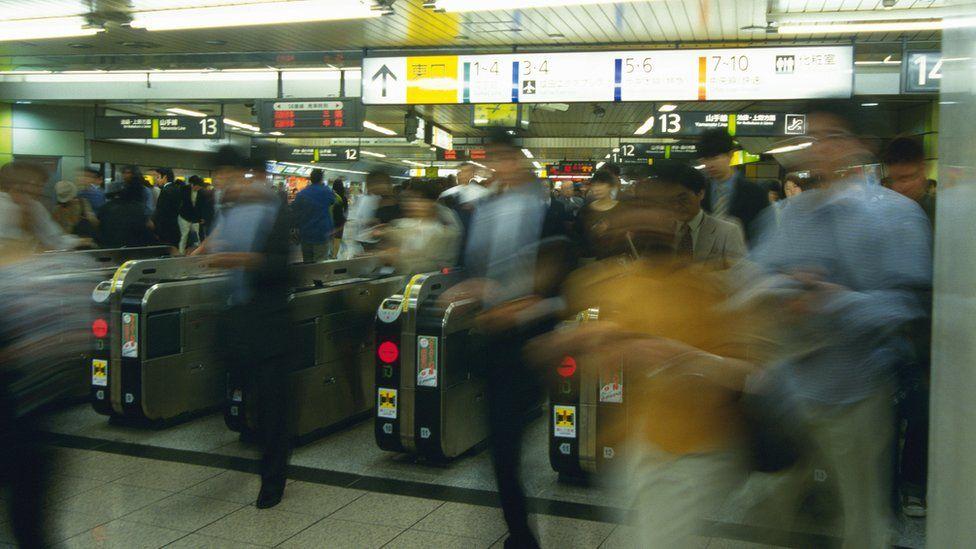 Blurred photo of travellers walking through ticket machines