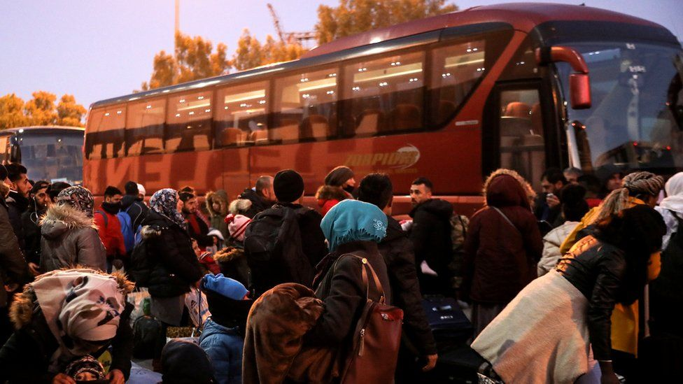 Refugees and migrants wait to board buses that will transfer them to the mainland following their arrival on a passenger ferry from the island of Lesbos at the port of Piraeus, 22 January 2020