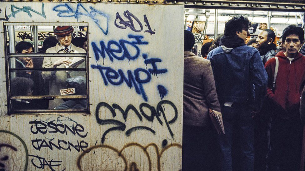 People on a New York Metro train in the early 1980s