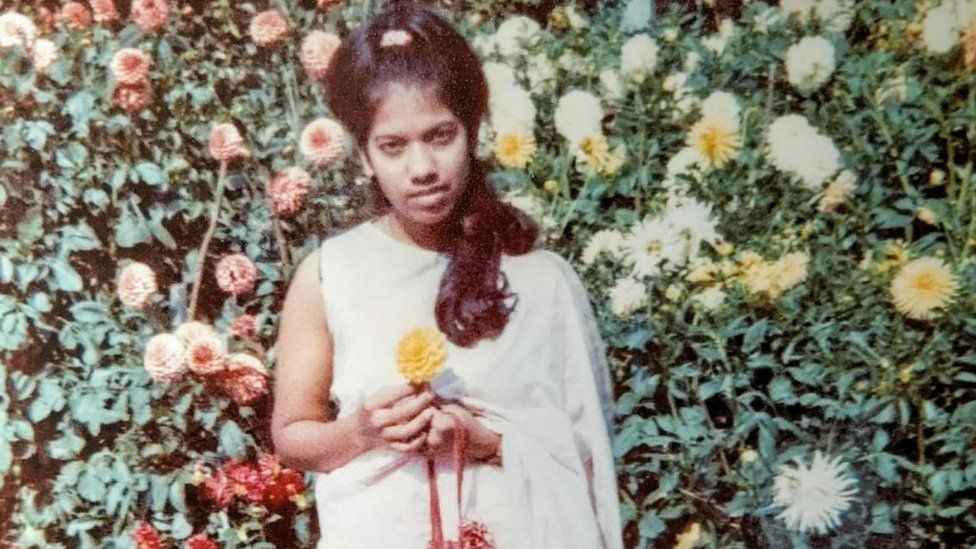 Rahima Sidhanee poses with a flower as a young woman after arriving in the UK in 1969