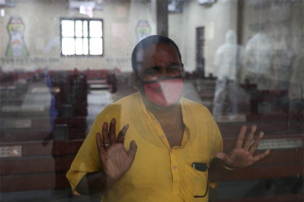 A relative leans against a glass window at the crematorium where a family member who died from the coronavirus disease (COVID-19) is prepared for cremation, in New Delhi, India, April 9, 2021.