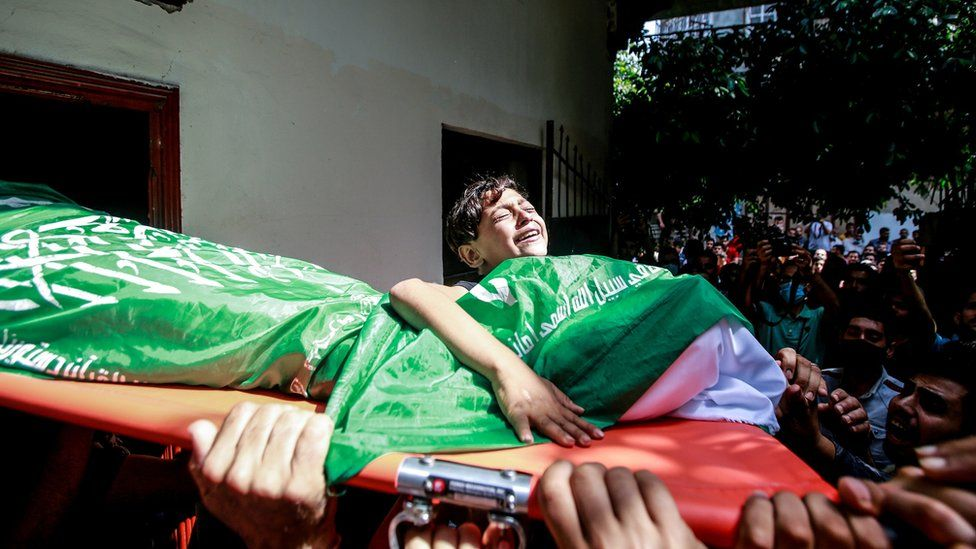 Palestinian boy holding stretcher during funeral