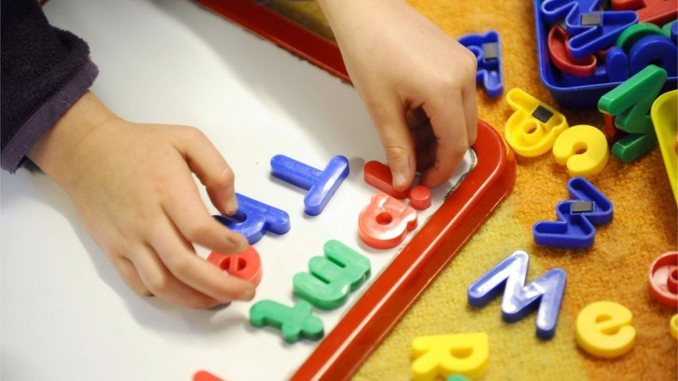 Child playing wit toy letters
