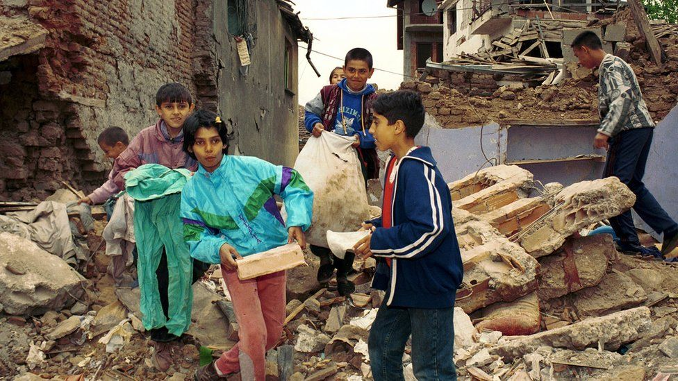 Children carrying rubble from a house destroyed by the attacks