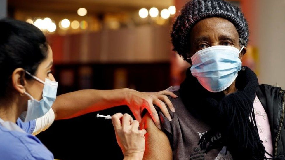A man wearing a face masking being vaccinated