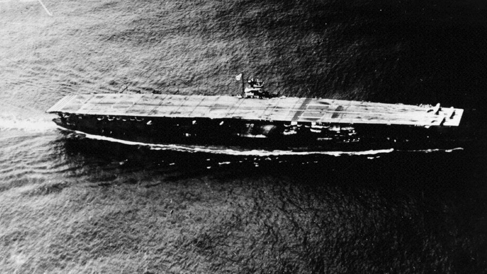 Black and white image shows the aircraft carrier on water