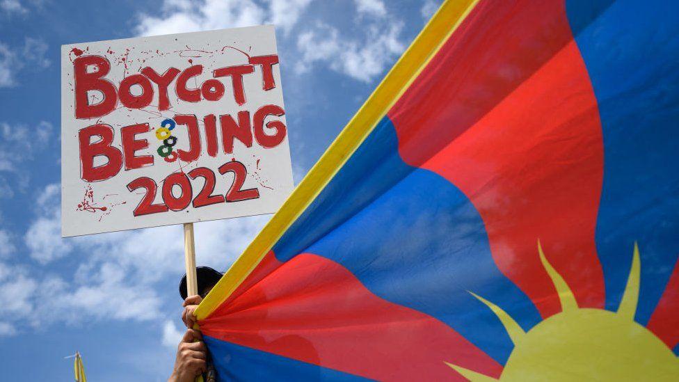 A Tibetan activist holds a placard and a Tibetan flag during a protest against Beijing 2022 Winter Olympics