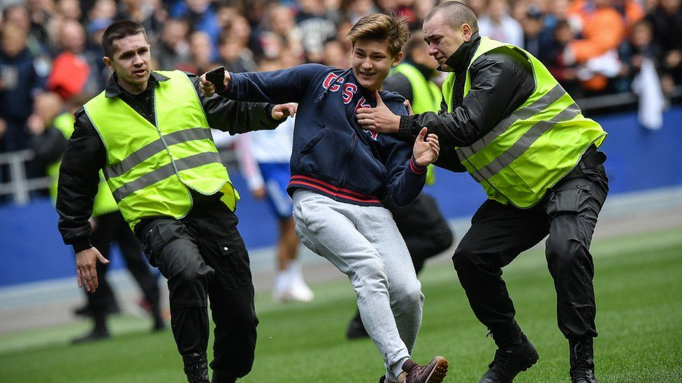 Security guards catch a pitch invader during a training session of the Russian national football team at Moscow's VEB Arena stadium on June 9, 2018