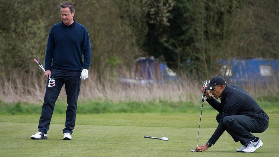 US President Barack Obama (R) lines up a putt as British Prime Minister David Cameron (L) looks on at at The Grove Golf Course near Watford in Hertfordshire.