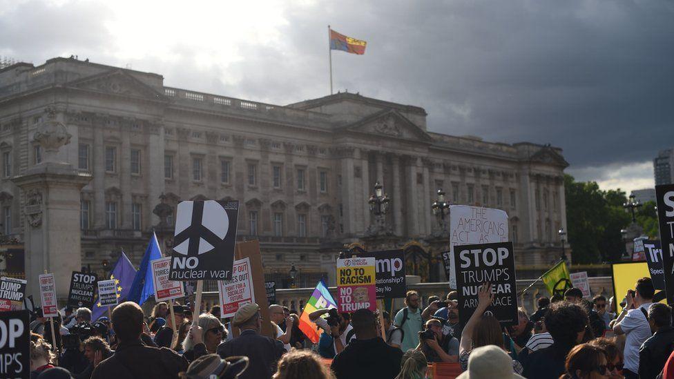 Manifestantes protestando contra Trump afuera del Palacio de Buckingham.