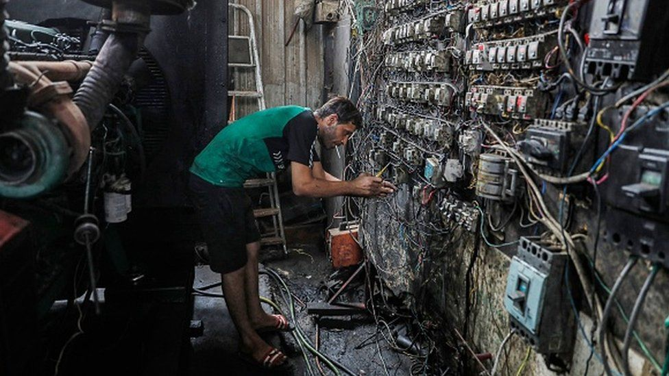 A technician controls an electric switch board connecting homes to privately owned electricity generators in a suburb of Iraq's capital Baghdad