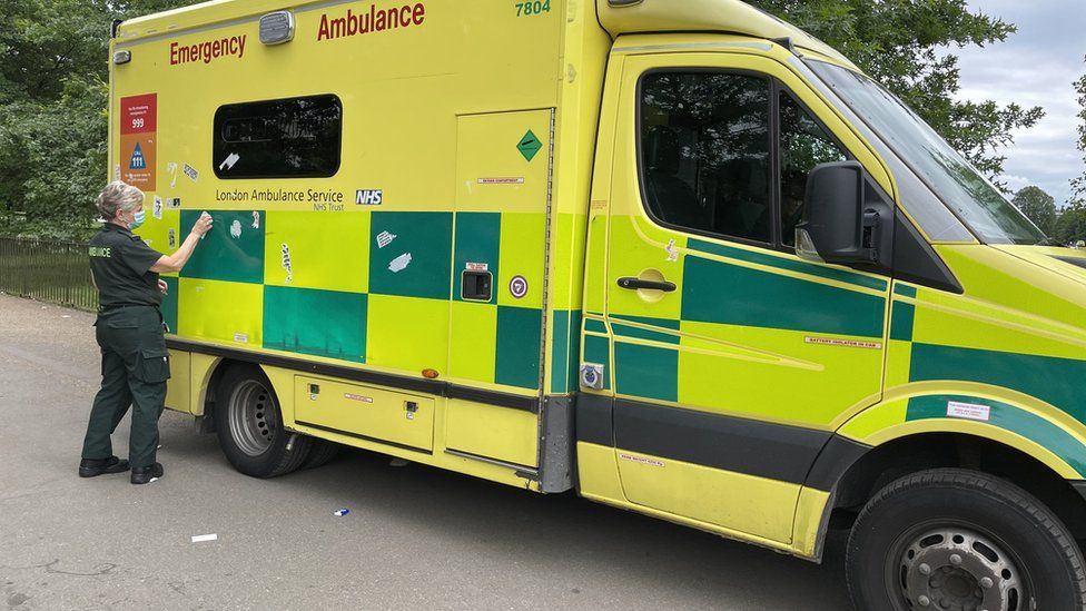 Adhesive stickers are removed from an ambulance in Hyde Park
