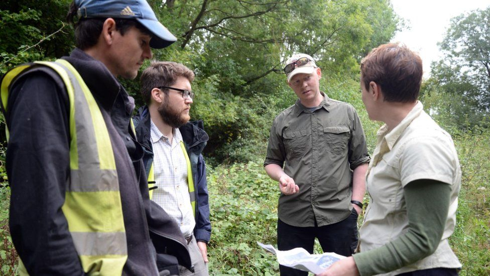 Stephen Humphreys (second from right), chief executive officer of the American Veterans Archaeology Recovery Program, discusses where to excavate next with expert and amateur archaeologists at an archaeological dig site