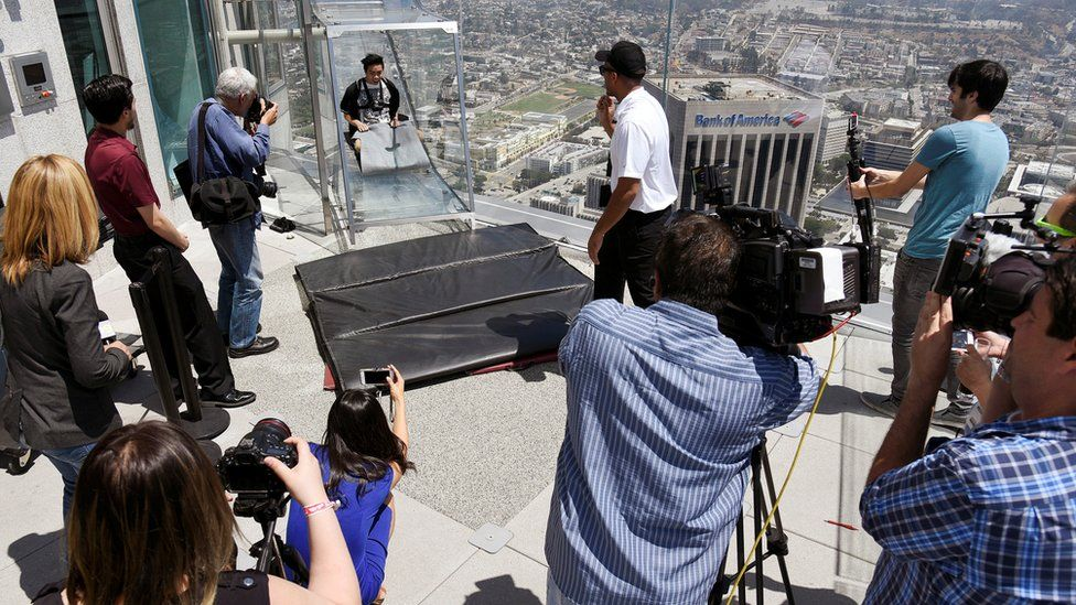 A man rides down a glass slide in Los Angeles