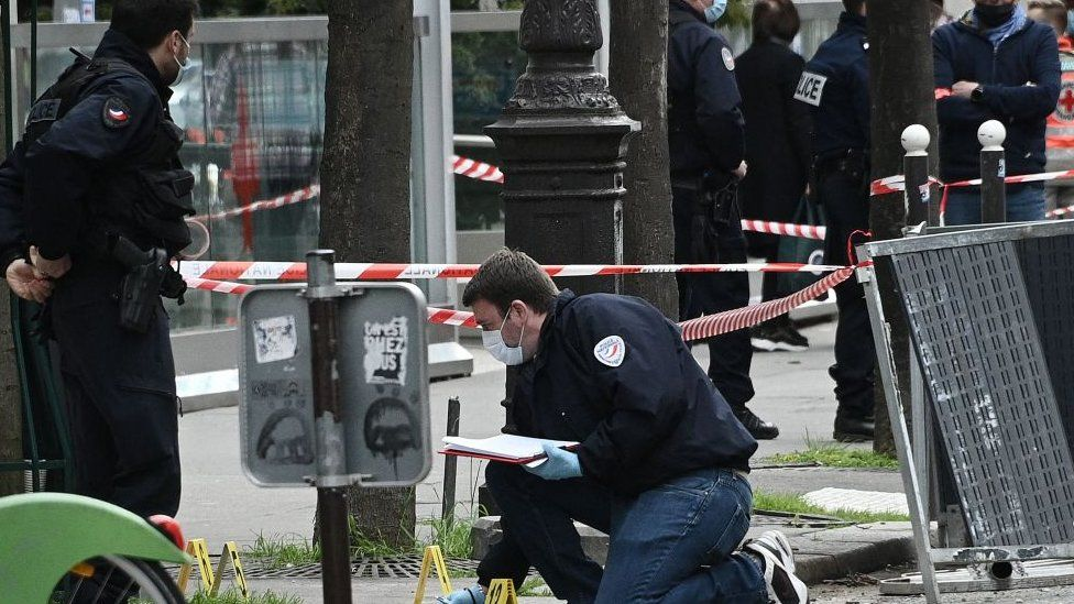 Police investigate the scene of a shooting outside a Paris hospital, 12 April 2021