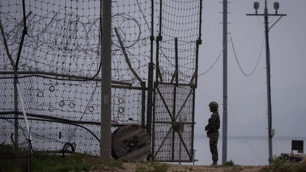 A soldier stands guard at an opening to the fence of the Demilitarized Zone (DMZ) during maintenance, on Gyodong, a tiny outlying island near to the west of Seoul, on 9 May 2017