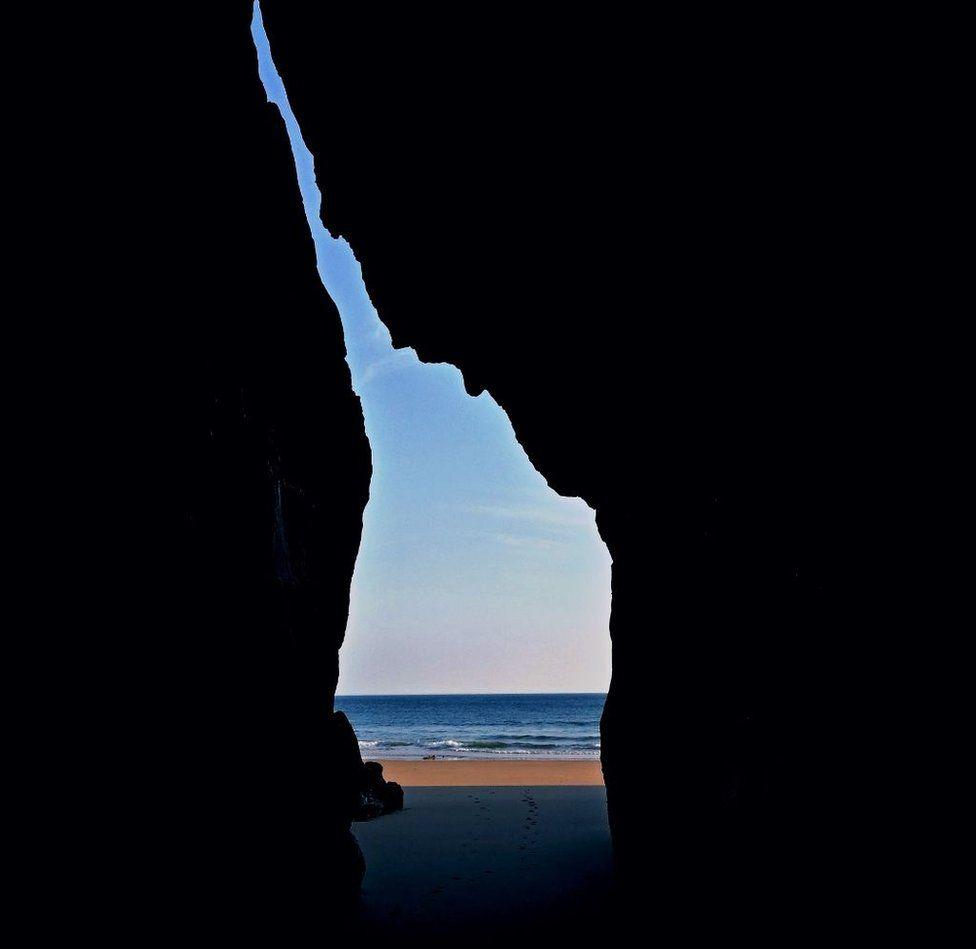 The beach through a crack in a rock