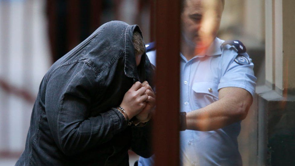 A police officer escorts Jaymes Todd, who is holding a jacket over his face, into the Victorian Supreme Court before his sentencing
