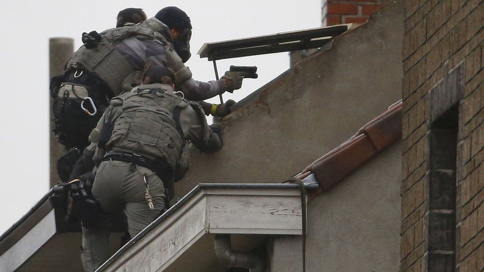 Belgian special forces police climb high on an apartment block during a raid, in search of suspected Muslim fundamentalists linked to the deadly attacks in Paris, in the Brussels suburb of Molenbeek