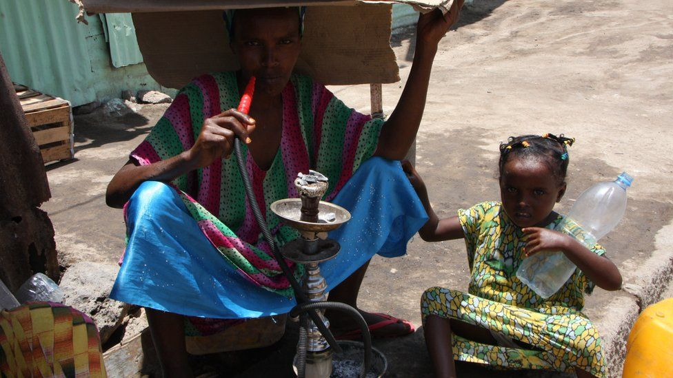 A woman smokes a shisha pipe covers her head from the sun along with a young girl in Djibouti