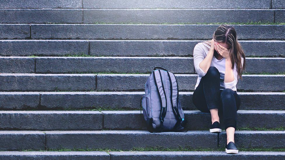 Distressed young woman with rucksack on steps (file image)