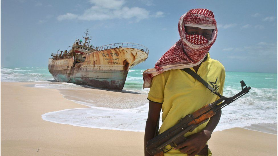 Masked and armed Somali pirate Hassan stands near a Taiwanese fishing vessel washed ashore in Hobyo, Somalia. 23 Sept 2012.
