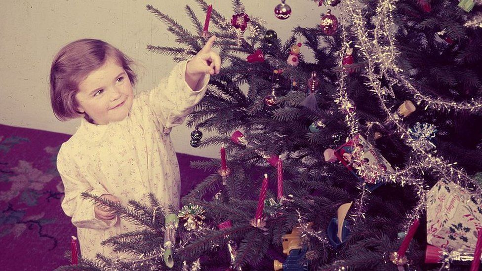 Girl looking at Christmas tree in the 1950s