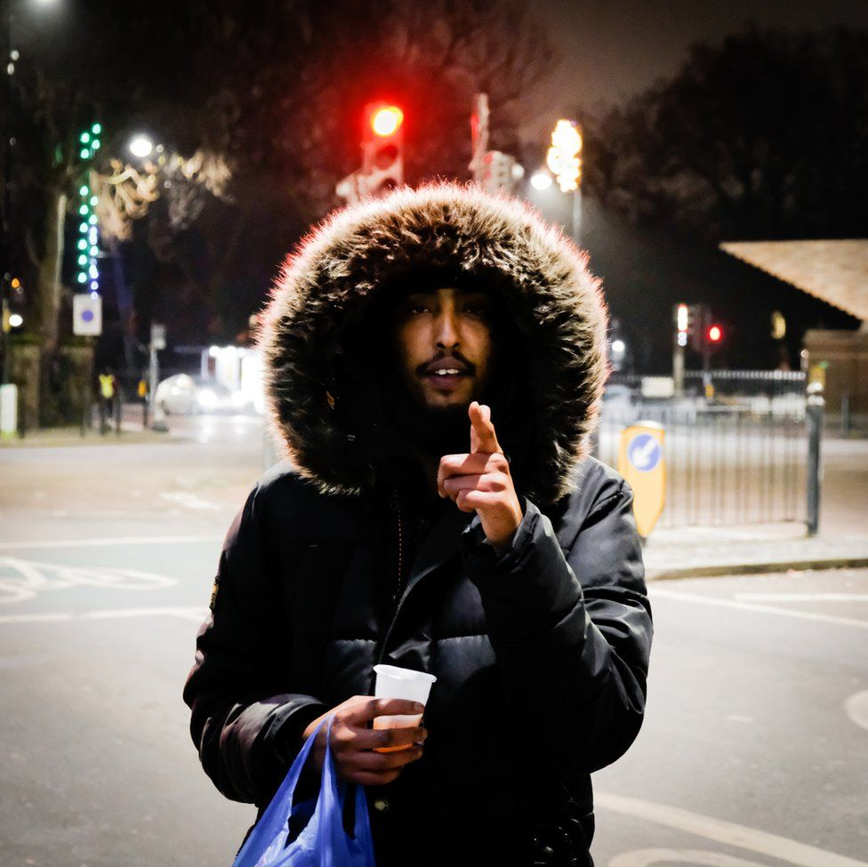 An image of a man with a big furry hood pointing at the camera