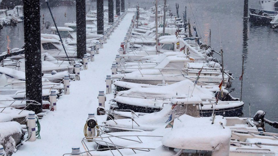 Snow covers boats moored at the port of San Sebastian after a snowstorm hit Basque Country, northern Spain