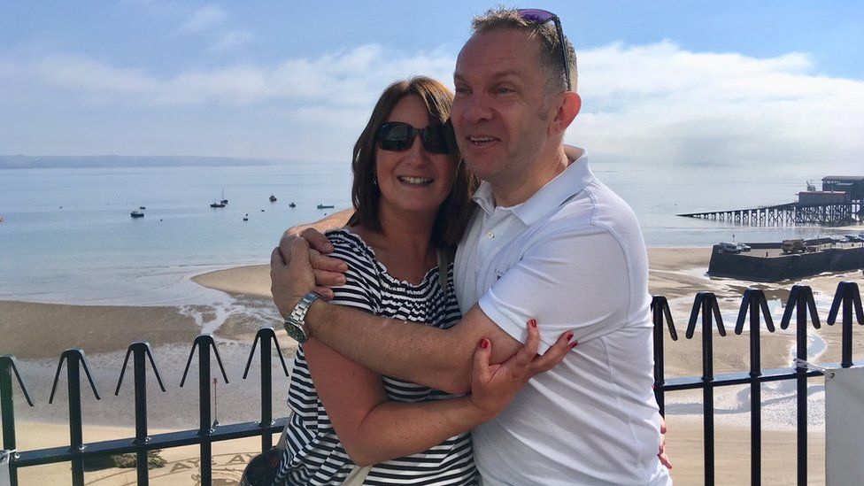 Emma Cornick and Neil Brierley hugging at Tenby beach after getting engaged
