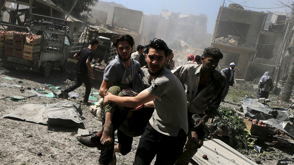 Men transport a casualty after what activists said were air strikes by government forces in the Damascus suburb of Douma (12 August 2015)