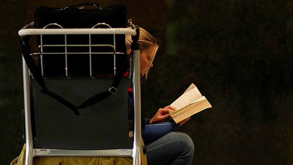 Woman sitting on airport trolley and reading