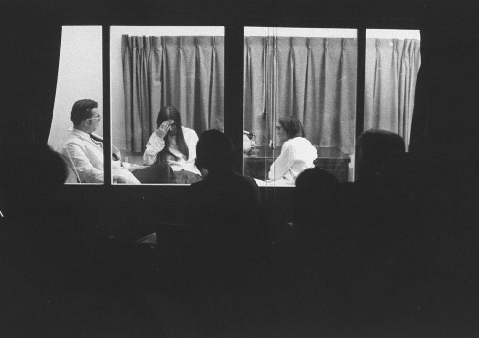 Elisabeth Kübler-Ross interviewing a woman with leukaemia in Chicago in 1969, with seminar participants behind a one-way mirror