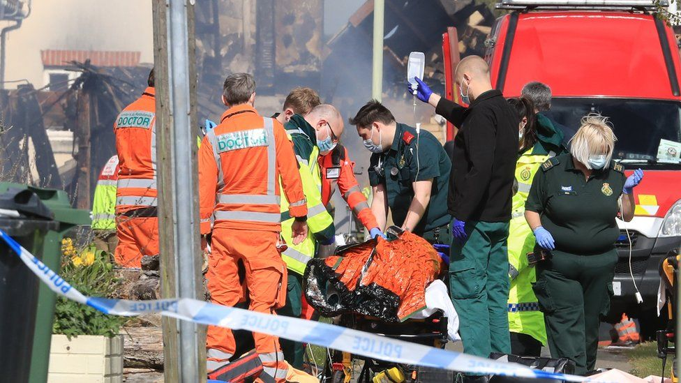 Paramedics attend to an injured person at the scene