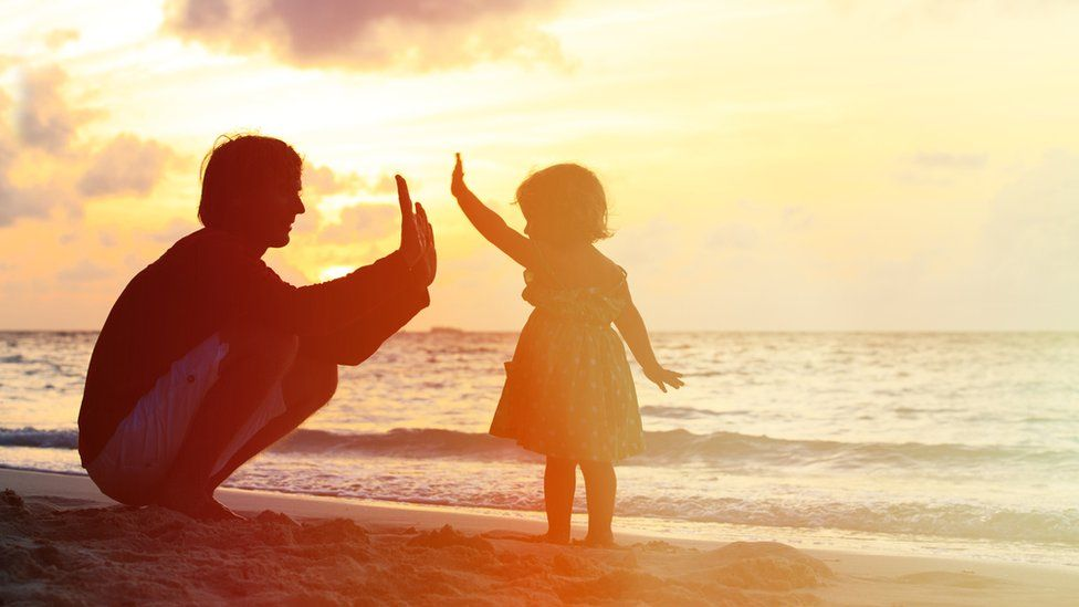Father and child playing on a beach
