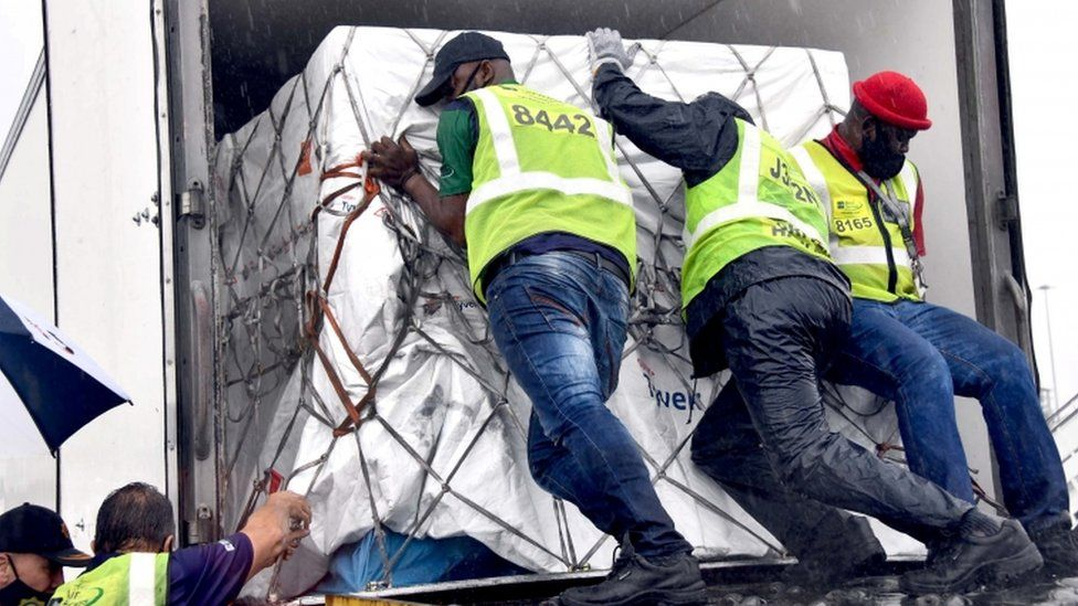 Workers unload the first vaccine shipment to arrive in South Africa