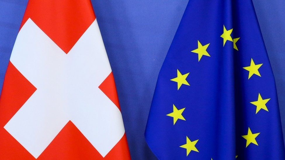 """Switzerland""""s national flag and the European Union flag are seen at the European Commission building in Brussels, Belgium April 23, 2021"""