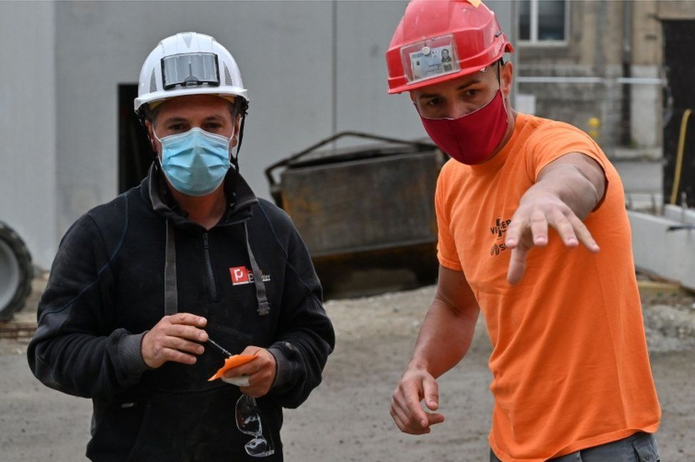 Construction workers wearing protective masks work on April 28, 2020, at a parking construction site in Chambery, eastern France