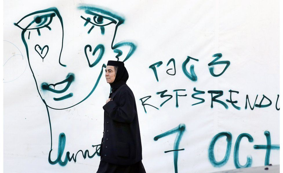 A Romanian Orthodox nun passes by a graffiti symbolizing the crying face of a LGBT community member on 5 Oct