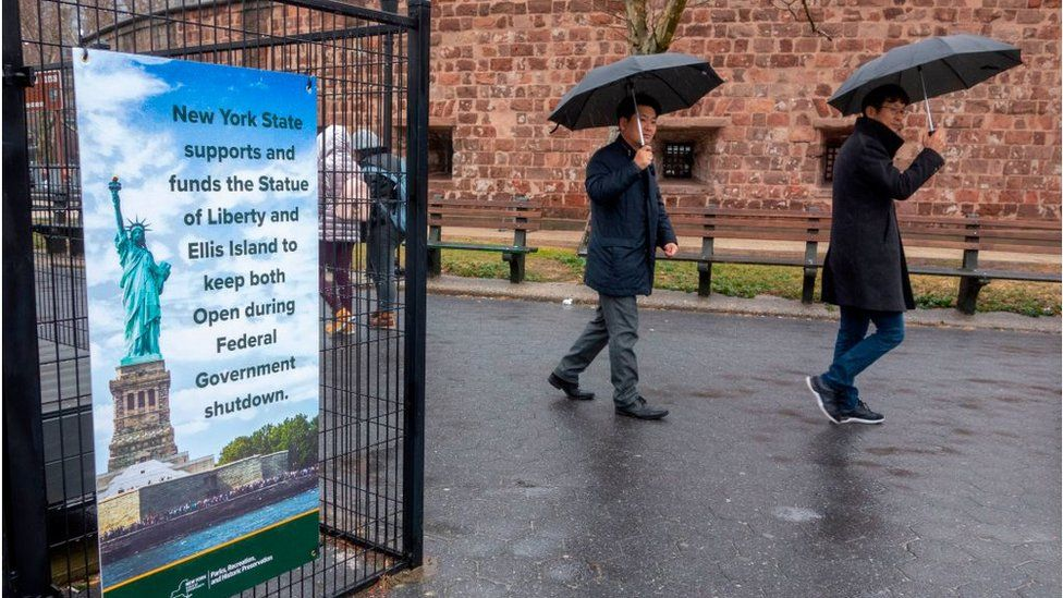 People walk past a sign announcing that New York funds are keeping the Statue of Liberty and Ellis Island open for visitors on January 5, 2019, in New York