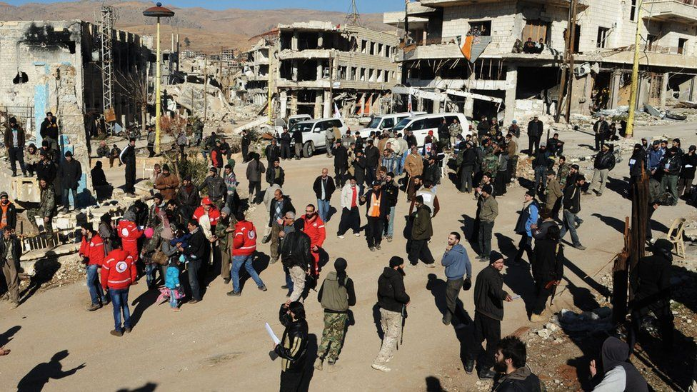 Syrian opposition fighters and their families gather at a square surrounded by damaged buildings, as they prepare to evacuate Zabadani town, Syria (photo from Syrian official news agency, Dec. 28, 2015)