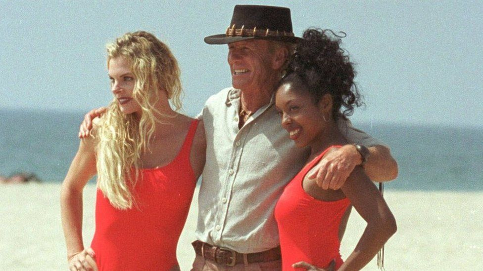 Paul Hogan poses with two women in swimsuits during filming for the 2001 film Crocodile Dundee in Los Angeles