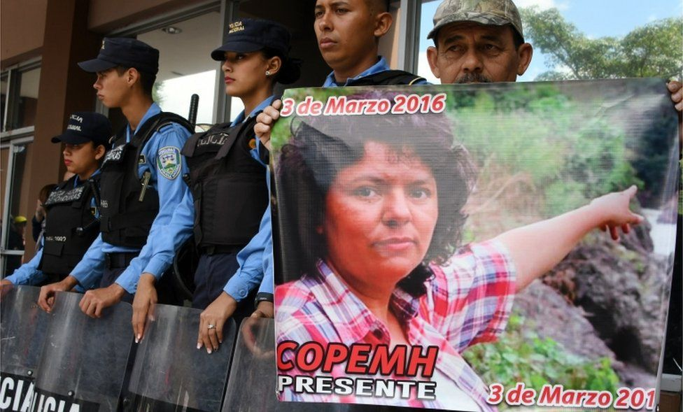 A man holds a poster during a protest demanding justice in the murder of Berta Caceres