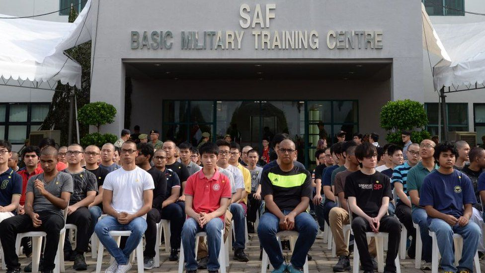 Incoming National Service recruits wait to take an oath