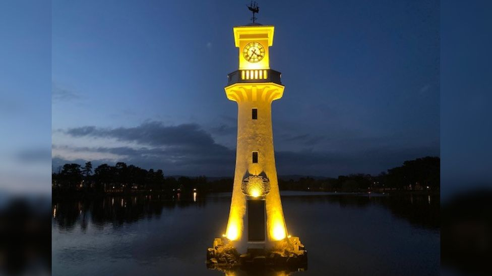 Roath Park clock tower lit up in yellow